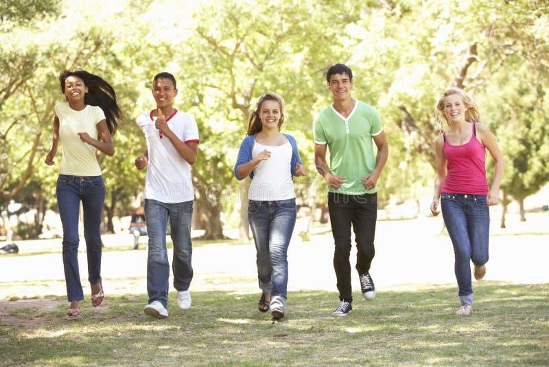Groupe d'amis adolescents courant en parc photos stock