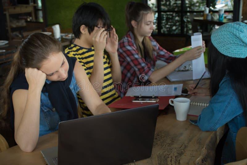 Groupe d'amis adolescents travaillant et se réunissant dans l'équipe avec des rapports et l'ordinateur portable sur la table en b photographie stock libre de droits