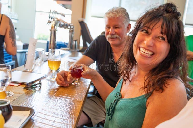 Groupe d'amis appréciant des verres de bière micro de brew à la barre image stock