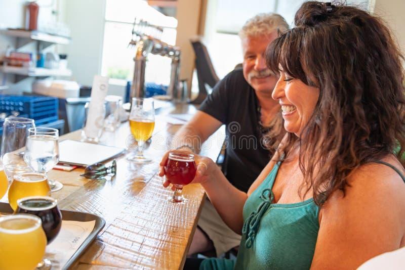 Groupe d'amis appréciant des verres de bière micro de brew à la barre images stock