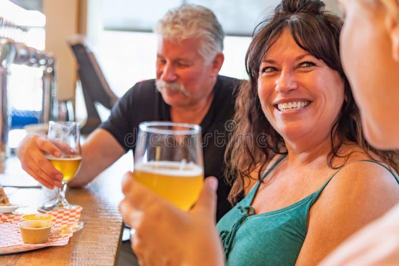 Groupe d'amis appréciant des verres de bière micro de brew à la barre photos libres de droits