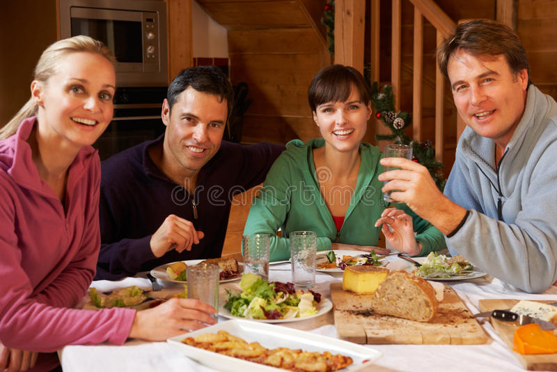 Groupe d'amis appréciant le repas dans le chalet alpestre photographie stock