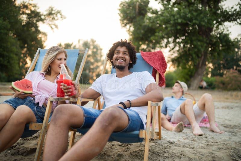 Groupe d'amis ayant l'amusement sur la plage ?t?, amusement, les gens, concept de vacances photographie stock libre de droits