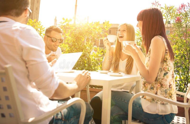 Groupe d'amis ayant un café extérieur photo libre de droits
