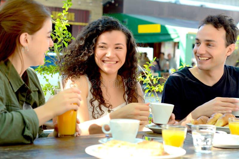 Groupe d'amis ayant un grand temps dans un caf? photographie stock libre de droits