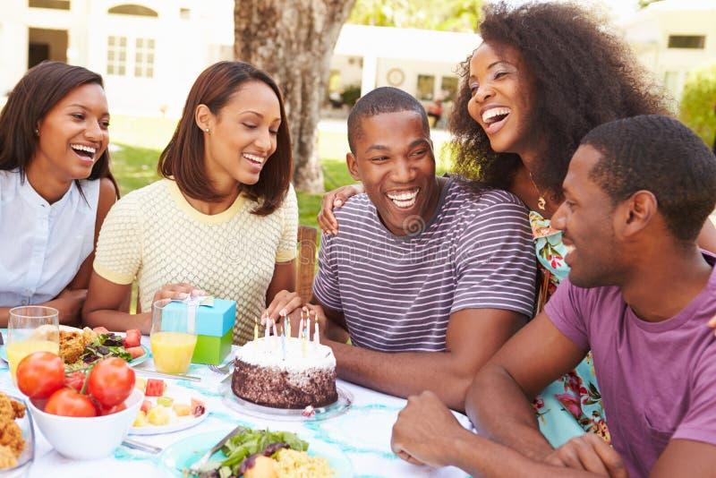 Groupe d'amis célébrant l'anniversaire à la maison photographie stock libre de droits