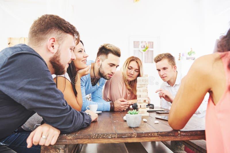 Groupe d'amis créatifs s'asseyant à la table en bois Les gens ayant l'amusement tout en jouant le jeu de société photo libre de droits