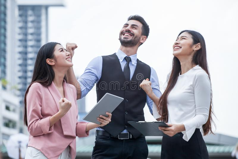 groupe d'amis de jeune homme et de femmes à l'aide d'un comprimé et riant dehors trois personnes de travail d'équipe excitant des image libre de droits