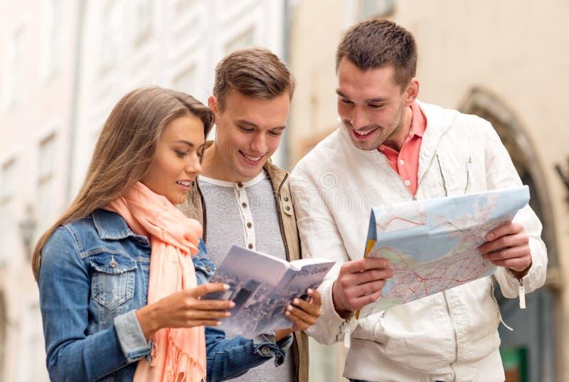 Groupe d'amis de sourire avec le guide et la carte de ville photo stock