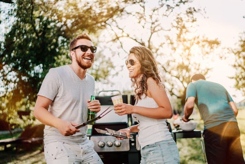 Groupe d'amis de sourire dans les vacances ayant des bières et faisant cuire sur le barbecue de jardin Mode de vie, concept de lo photographie stock