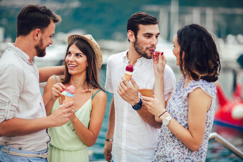 Groupe d'amis de sourire mangeant la crème glacée  images stock