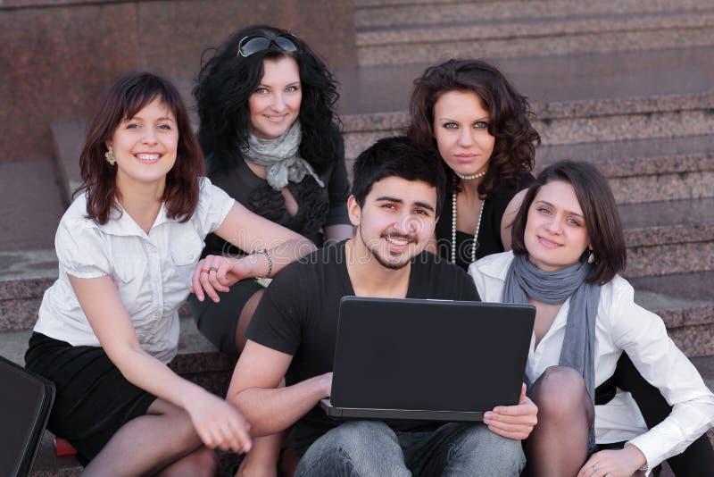 Groupe d'amis des ?tudiants avec un ordinateur portable photographie stock libre de droits