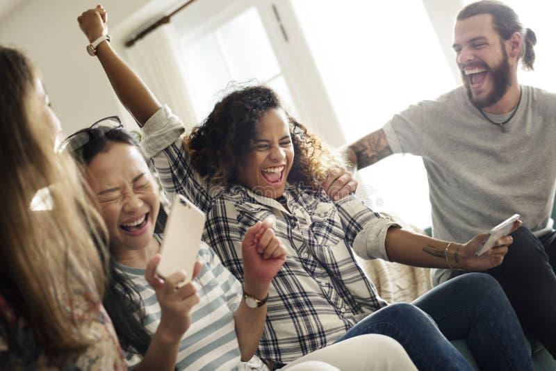 Groupe d'amis divers jouant le jeu au téléphone portable photos libres de droits