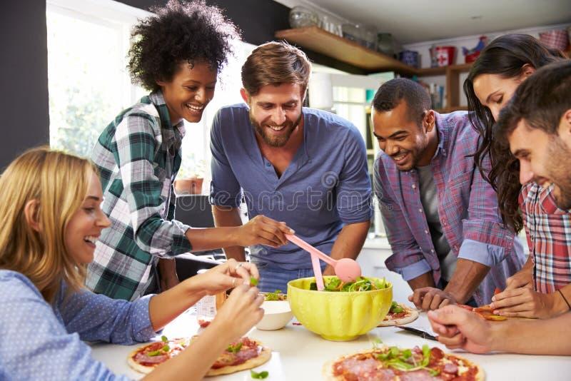 Groupe d'amis faisant la pizza dans la cuisine ensemble image stock
