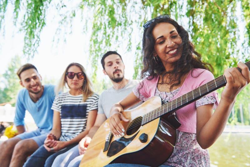 Groupe d'amis heureux avec la guitare Tandis que l'un d'entre eux joue la guitare et d'autres lui donnent une salve d'applaudisse photographie stock libre de droits