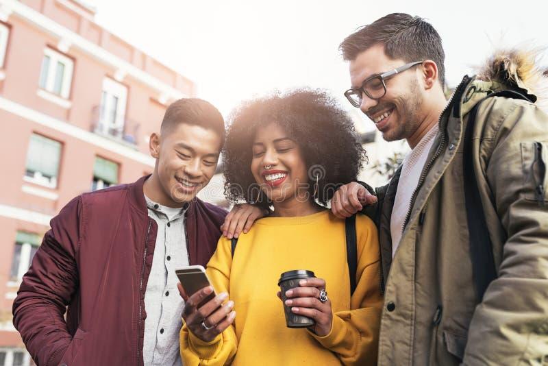 Groupe d'amis heureux employant le mobile dans la rue image libre de droits