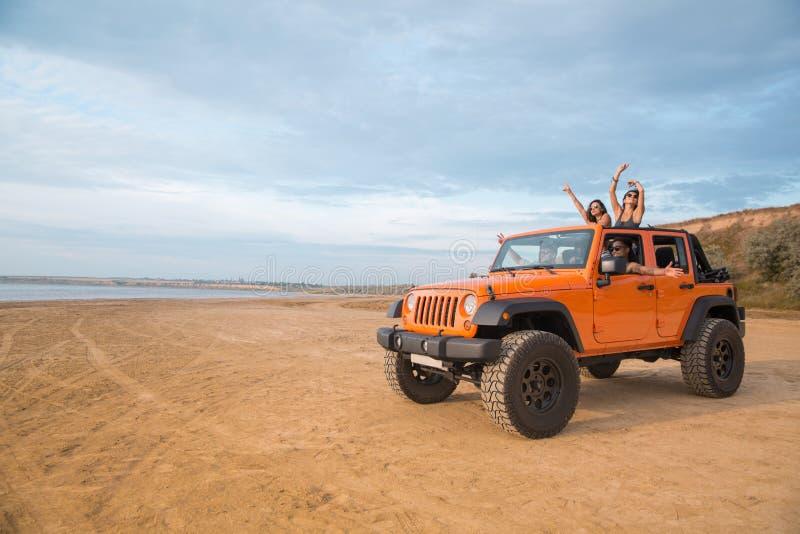 Groupe d'amis heureux enthousiastes se tenant dans une voiture photographie stock libre de droits
