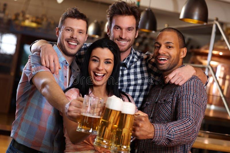 Groupe d'amis heureux faisant tinter avec de la bière dans le bar images stock