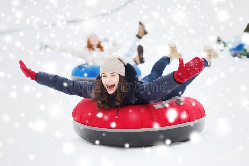 Groupe d'amis heureux glissant vers le bas sur des tubes de neige image libre de droits