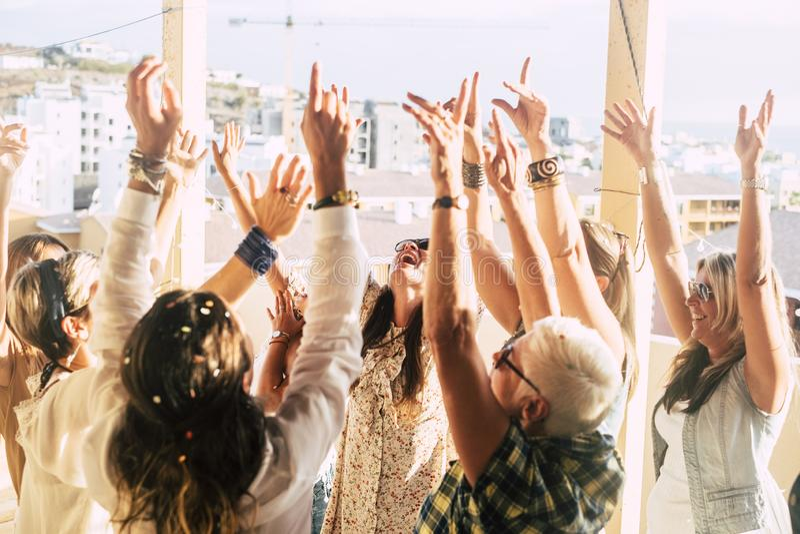 Groupe d'amis jeunes et femmes âgées fêtent avec des confettis en plein air avec vue sur la ville - concept d'amitié image libre de droits