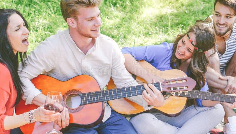 Groupe d'amis jouant des guitares et chantant tout en buvant du vin rouge se reposant sur l'herbe en parc ext?rieur images stock