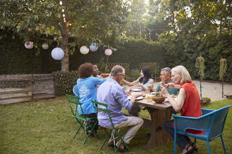 Groupe d'amis mûrs appréciant le repas extérieur dans l'arrière-cour image stock