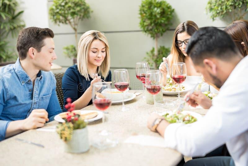 Groupe d'amis mangeant dans un restaurant photos libres de droits