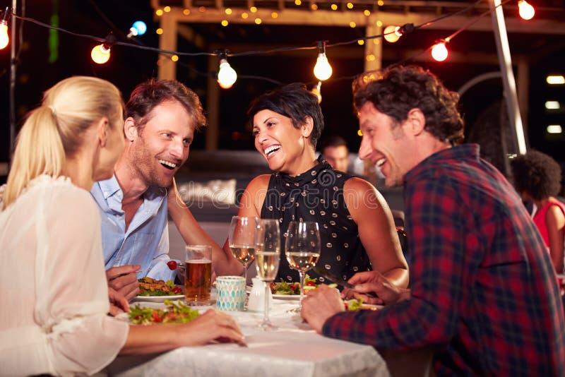 Groupe d'amis mangeant le dîner au restaurant de dessus de toit photo libre de droits