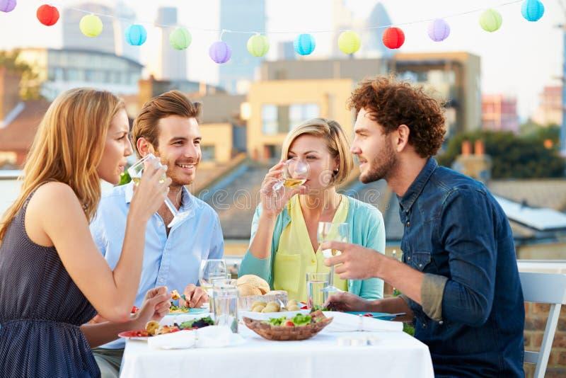 Groupe d'amis mangeant le repas sur la terrasse de dessus de toit image libre de droits