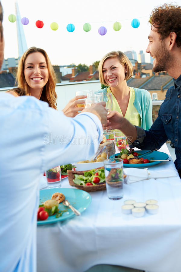 Groupe d'amis mangeant le repas sur la terrasse de dessus de toit images libres de droits