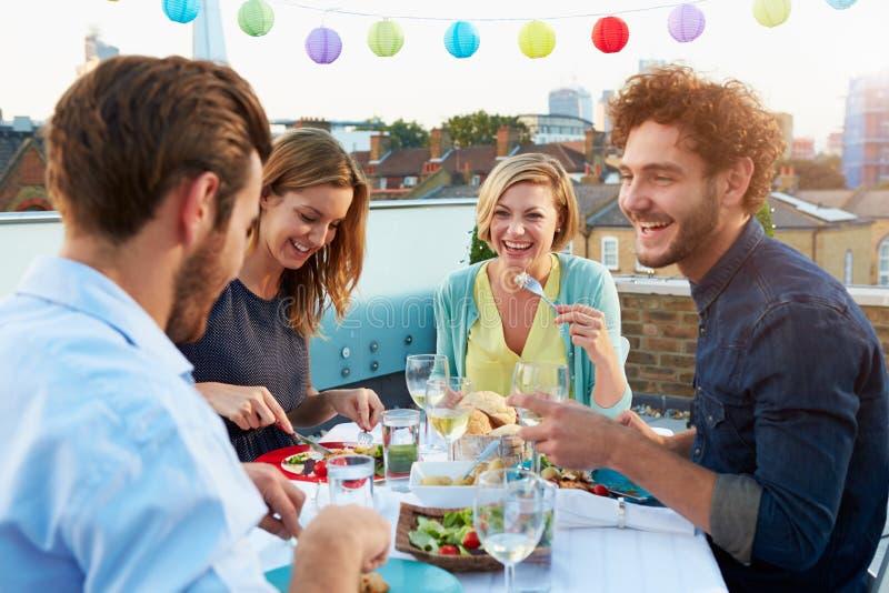Groupe d'amis mangeant le repas sur la terrasse de dessus de toit photographie stock