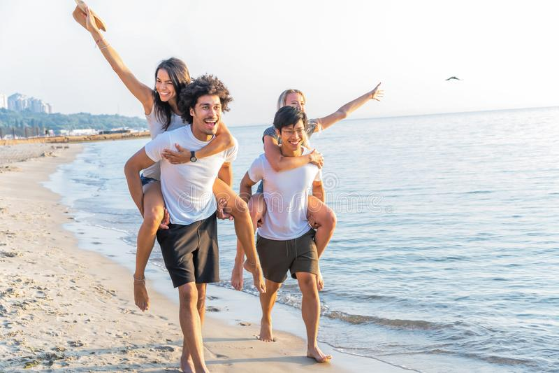 Groupe d'amis marchant le long de la plage, avec les hommes donnant sur le dos le tour aux amies Jeunes amis heureux appréciant a photos stock