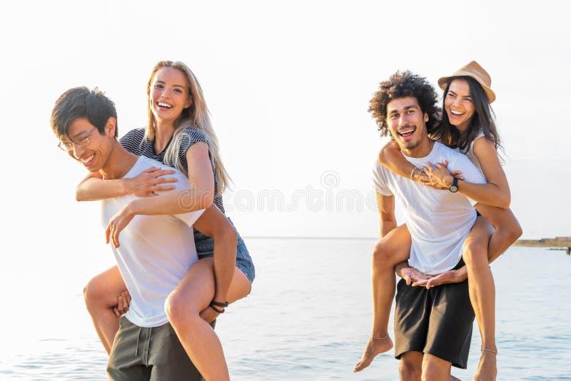 Groupe d'amis marchant le long de la plage, avec les hommes donnant sur le dos le tour aux amies Jeunes amis heureux appréciant a images libres de droits