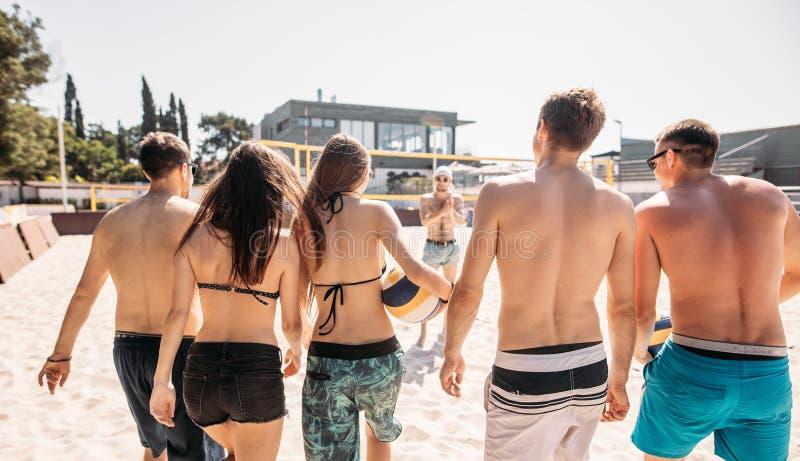 Groupe d'amis marchant sur la cour de volleyball de plage au matin ensoleillé image libre de droits