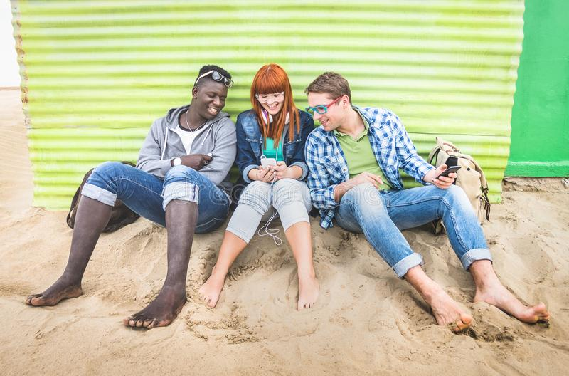Groupe d'amis multiraciaux heureux ayant l'amusement ensemble utilisant le téléphone portable photos stock