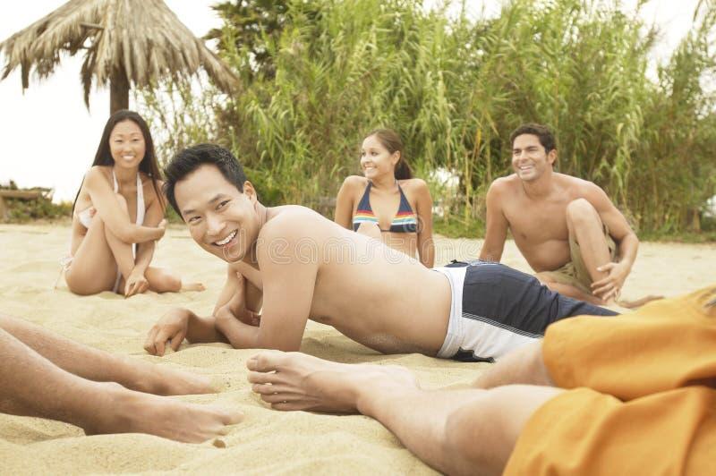 Groupe d'amis parlant sur la plage photographie stock