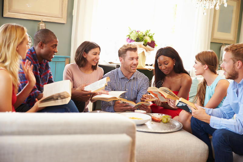 Groupe d'amis participant dans le club de lecture à la maison images stock