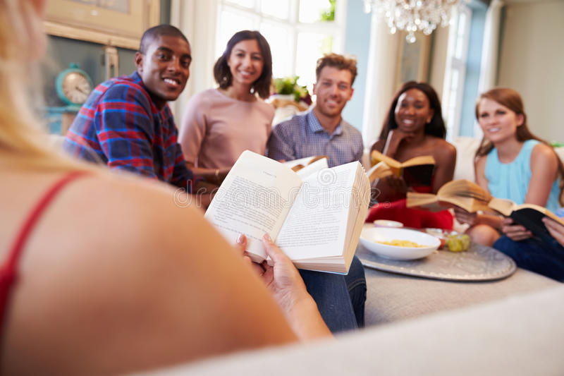 Groupe d'amis participant dans le club de lecture à la maison photographie stock
