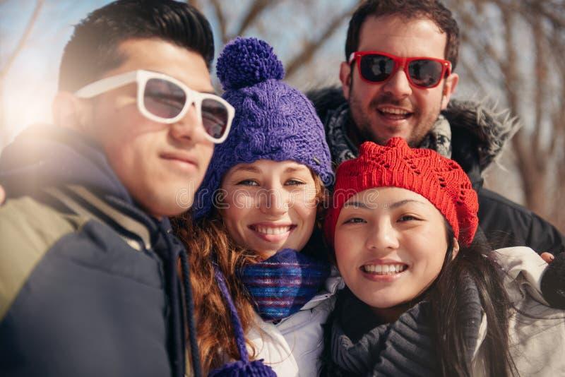 Groupe d'amis prenant un selfie dans la neige en hiver images stock