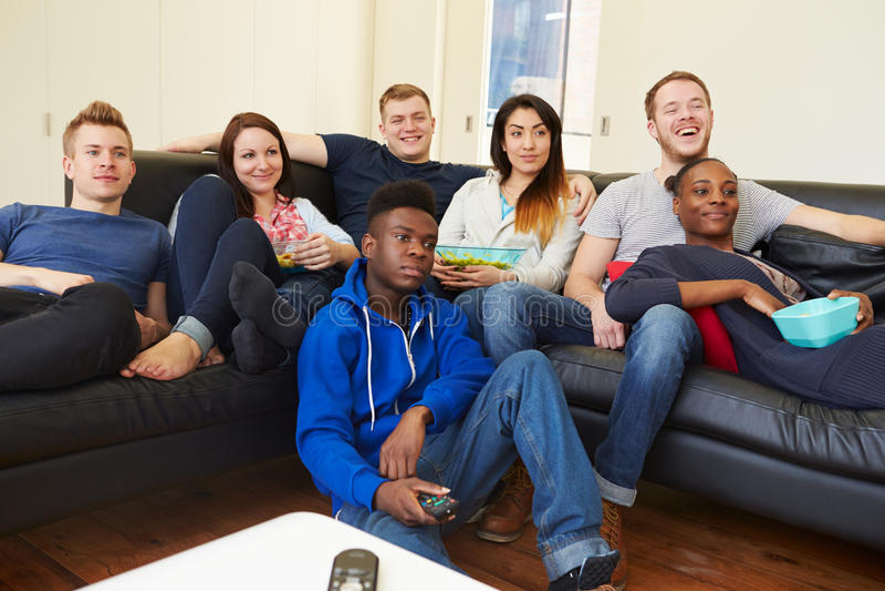 Groupe d'amis regardant la télévision à la maison ensemble photos stock