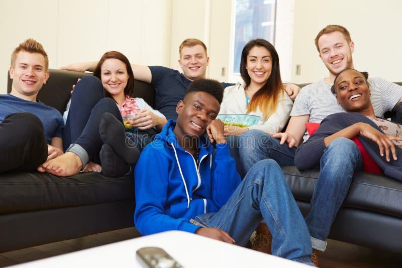Groupe d'amis regardant la télévision à la maison ensemble images libres de droits