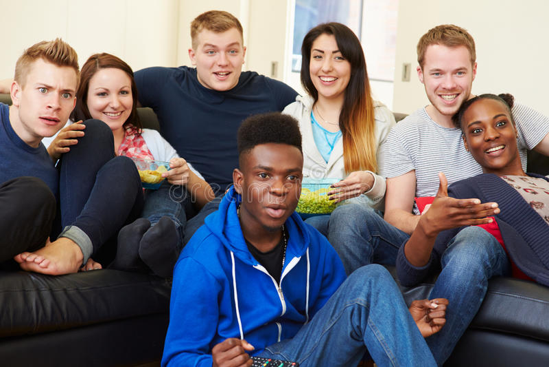 Groupe d'amis regardant la télévision à la maison ensemble photo stock