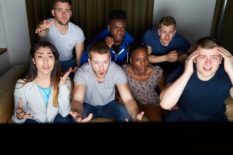 Groupe d'amis regardant la télévision à la maison ensemble photographie stock