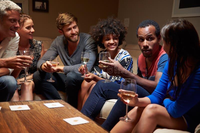 Groupe d'amis s'asseyant autour d'une table à la partie de maison image stock