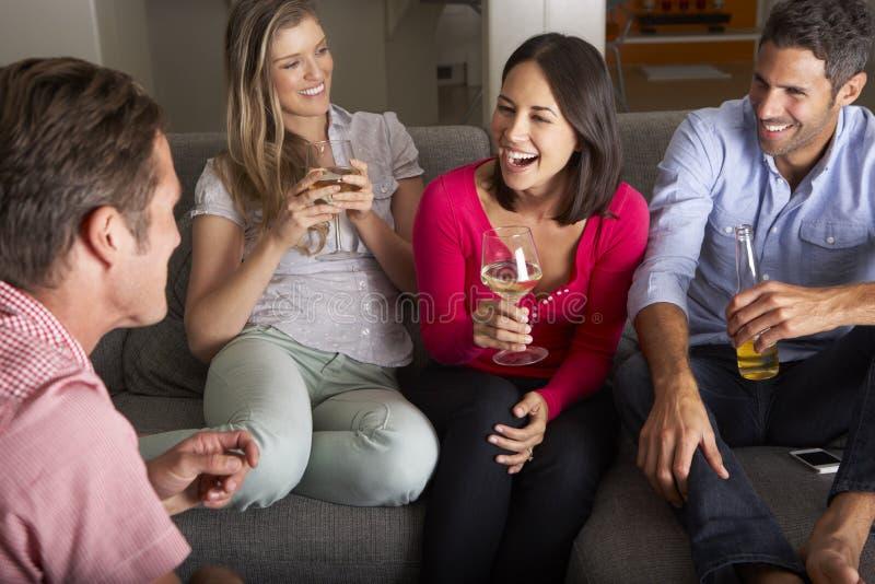 Groupe d'amis s'asseyant sur Sofa Talking And Drinking Wine image libre de droits