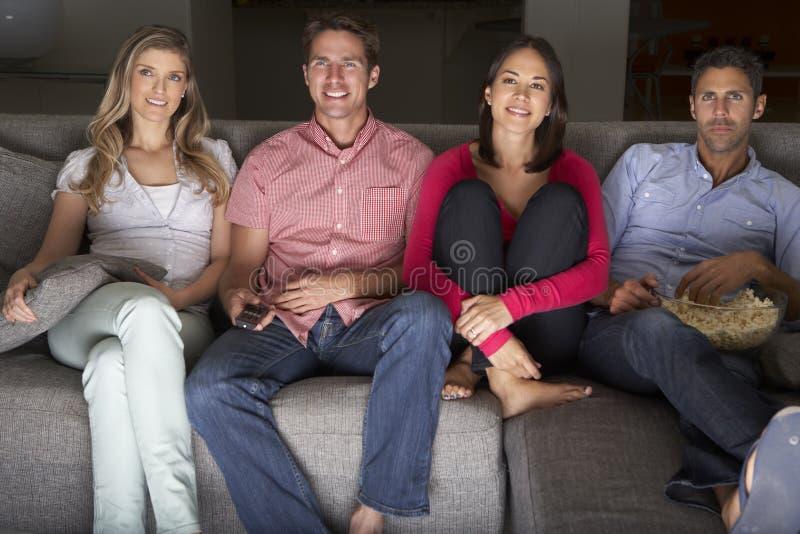 Groupe d'amis s'asseyant sur Sofa Watching TV ensemble photos libres de droits