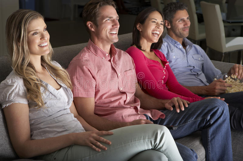Groupe d'amis s'asseyant sur Sofa Watching TV ensemble photos libres de droits
