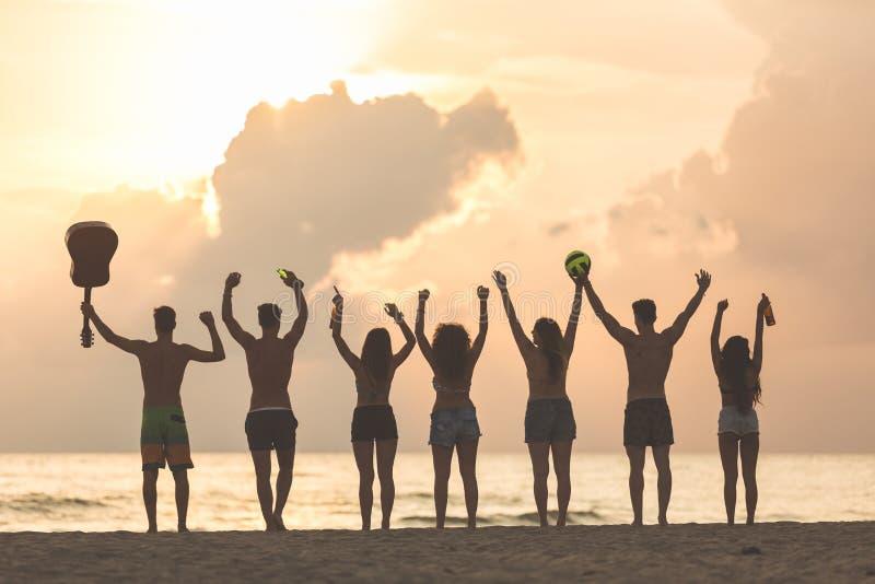 Groupe d'amis soulevant des mains sur la plage au coucher du soleil photographie stock