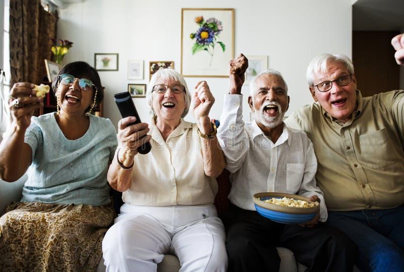 Groupe d'amis supérieurs gais reposant et regardant la TV ensemble photo libre de droits