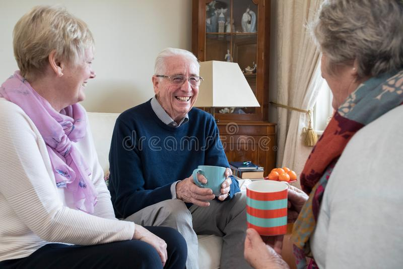 Groupe d'amis supérieurs se réunissant à la maison pour le café photographie stock libre de droits